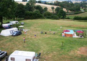 Afbeelding van ons campingterrein. Mensen zijn aan het tennissen, zwemmen en zitten op het terras.