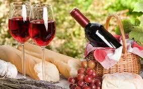 Picknick mand met kaas, stokbrood en een mooie fles wijn.